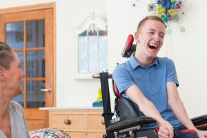 Man in wheelchair laughing with a woman