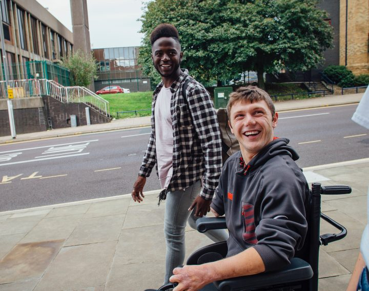 Amputee male in wheel chair on street with friends