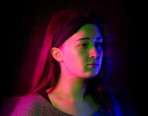 Young woman in front of dark background bathed in colour light