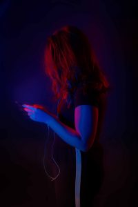 Woman facing away from camera bathed in coloured light