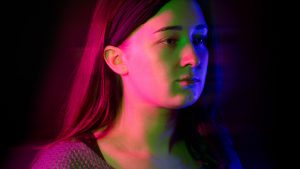 Young woman looking forward in front of dark background bathed in colour light