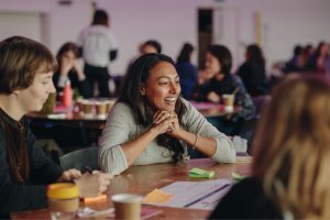 Woman laughing during table discussion