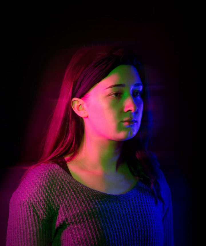 Young woman looking forward bathed in coloured light and shadow