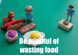 """a poster saying """"be mindful with wasting food"""" and showing a child with a lot of food and the other with very little food."""