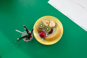 A green school desk with a bowl of fruit, a teaspoon, work sheet and a cup of colouring pencils.