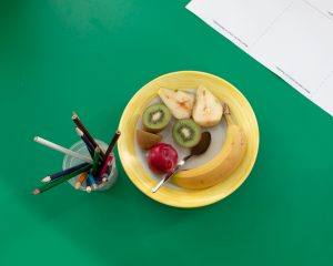 a plate of mixed fruit with a pot full of pencils and pens on a school desk