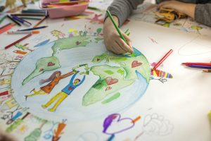 a photograph of children's hands drawing a picture of the planet and people linking hands around it
