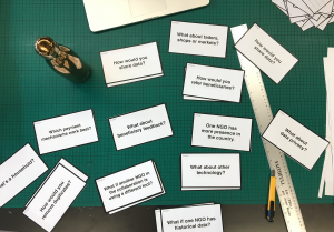 a photograph of a table top with lots of small white cards with What If statements on