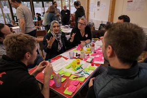 a photo taken at a codesign workshop showing people sitting around a table covered with post it notes and pens, chatting about ideas