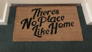a photograph of a doormat with the text 'There's No Place Like Home' on it